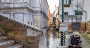 """a gondolier waiting for customers in front of a sign saying """"gondola service"""""""