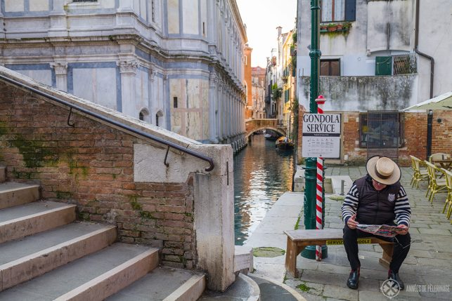 "a gondolier waiting for customers in front of a sign saying ""gondola service"""