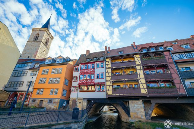 THe fantastic krämerbrücke with colorful half-timbered houses lining the lenght of the bridge in Erfurt with the Aägiden church