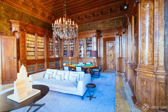 The ancient library on the second floor of AMan Venice, with leather tapestries and ornate wooden book cases