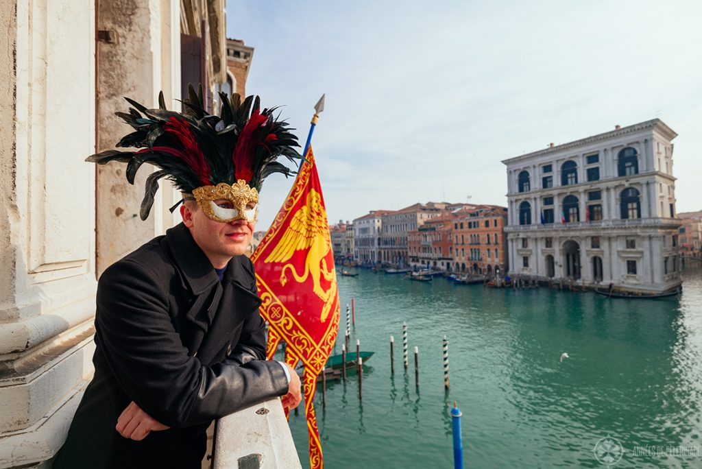 Me wearing a carnival mask with black and red feathers on the balcony of the Aman venice hotel at the Canal Grande