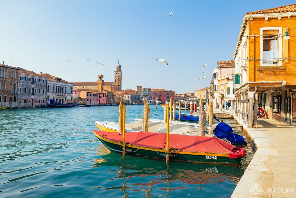 View along the main water channel through the Island of Murano near Venice with three storied colorful houses on each side an a couple of boats in the foreground