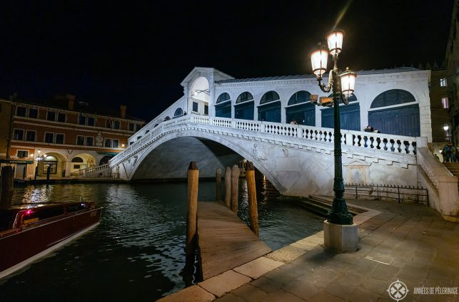 The Rialto bridge in Venice at night with a street lantern and a little empty board pier in the foreground