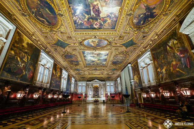 The grand chapterhouse hall on the second floor of the Scuolla grande di San Rocco in Venice with an ornate golden ceiling and religious paintings by tiepolo