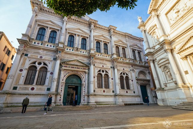 The ornate marble facade of the Scuola Grande di San Rocco with many false pillars and abstract stone carvings