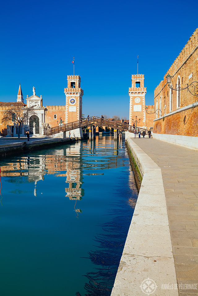 The entrance of the Venetian arsenal with two red brick towers to each side of the water channel and a bridge across it