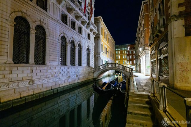 a beautiful little canal with a marble bridge and a palace in Venice at night