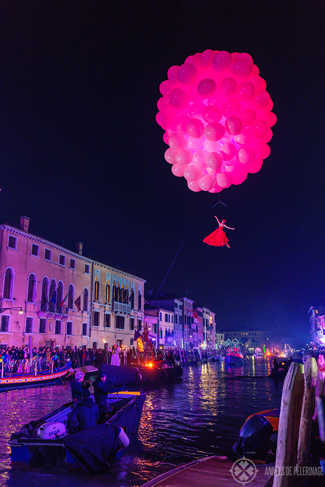 An acrobat attachted to a gigantic red baloon over the water channels of venice at night during carnival