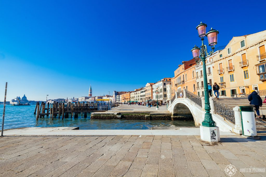 A bridge at the waterfront of Venice with St. Mark'S belltower in the far background