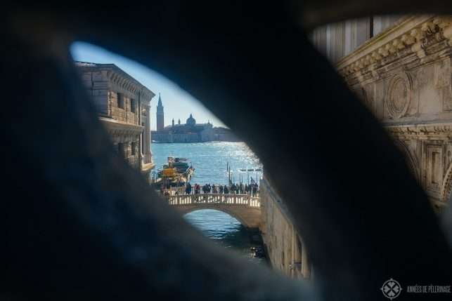 View of a bridge through the very thing viewing slits in the bridge of sighs in Venice